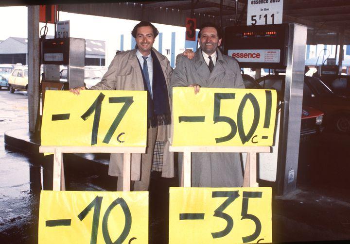 Edouard Leclerc (droite) et son fils Michel-Edouard font la publicité de leurs promotions à Brest (Finistère) devant une station d'essence, le 26 janvier 1985. (ANDRE DURAND / AFP)