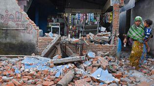 Une femme et son enfant, dans les débris d'un bâtiment effondré, après le séisme qui a touché l'île de Lombok (Indonésie), àLendang Bajur Hamlet, le 6 août 2018. (ANTARA FOTO AGENCY / REUTERS)