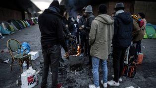 Des migrants se réchauffent autour d'un brasero et d'un repas fourni par une association à Saint-Denis en région parisienne. (CHRISTOPHE ARCHAMBAULT / AFP)