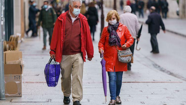 Deux personnes portent le masque dans une rue de Burgos, en Espagne, le 21 octobre 2020. (CESAR MANSO / AFP)