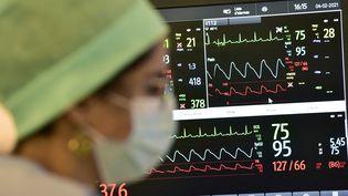 Une infirmière se tient devant un écran de contrôle des fonctions vitales d'un patient dans le service Covid-19 de l'hôpital Purpan de Toulouse, le 4 février 2021. (GEORGES GOBET / AFP)