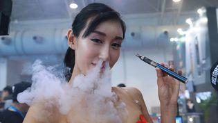 Unedémonstratrice fume une cigarette électronique lors d'une salon d'exposition, le 23 juillet 2015 à Pékin (Chine). (AFP)