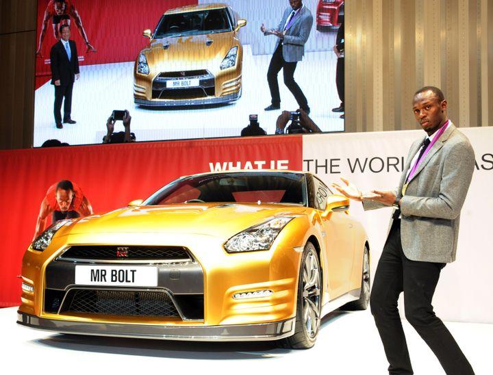 Le champion olympique Usain Bolt pose près d'un Nissan GT-R doré, à Yokohama (Japon), le 11 octobre 2012. (RIE ISHII / AFP)