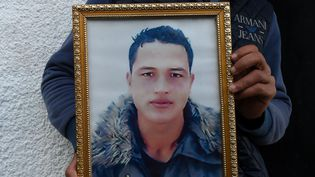 Le portrait d'Anis Amri, l'auteur présumé de l'attentat de Berlin, brandi par son frère à Oueslatia (Tunisie), le 23 décembre 2016. (FETHI BELAID / AFP)