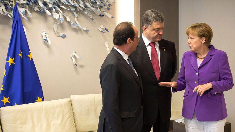 François Hollande (G.),Petro Porochenko etAngela Merkel, lors d'une rencontre à Bruxelles (Belgique), le 27 juin 2014. (GUIDO BERGMANN / DPA / AFP)