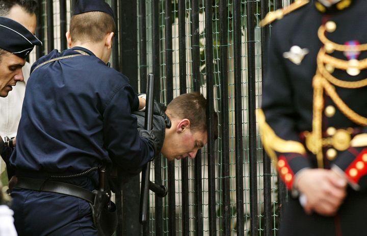 Des policiers maîtrisent Maxime Brunerie après qu'il a tiré sur Jacques Chirac sur les Champs-Elysées,le 14 juillet 2002. (PHILIPPE DESMAZES / AFP)