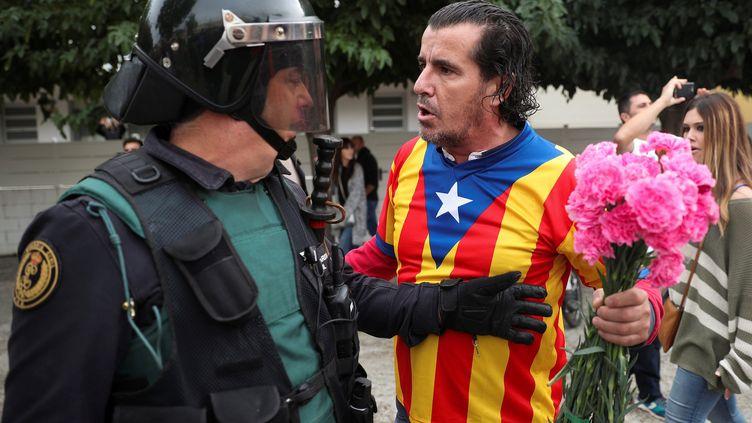 Unpartisan du référendum d'indépendance en Catalogne face à un policier espagnol, le 1er octobre 2017 à Barcelone. (ALBERT GEA / REUTERS)