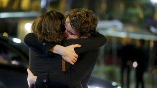 Des proches devant le Bataclan après la prise d'otages meurtrière dans la salle de concert, à Paris, le 14 novembre 2015. (CHRISTIAN HARTMANN / REUTERS)