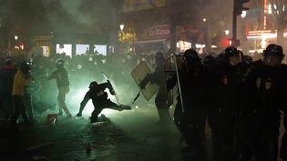 Un policier est poussé au sol par des casseurs, le 28 novembre 2020, à Paris. (THOMAS COEX / AFP)