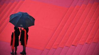 Des hotesses attendent avec un parapluie des invités sur le tapis rouge du Festival de Cannes en 2018. (ANNE-CHRISTINE POUJOULAT / AFP)
