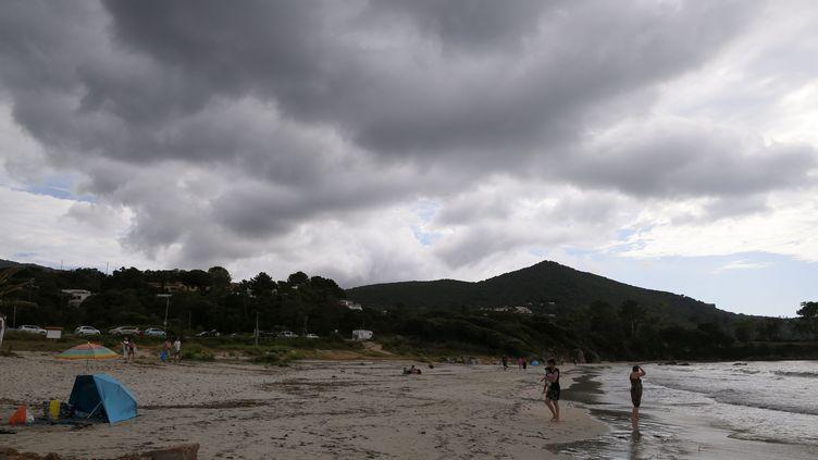 Des baigneurs sur la plage deMare e Sole, alors qu'un orage approche, le 14 juin 2018. (PASCAL POCHARD-CASABIANCA / AFP)