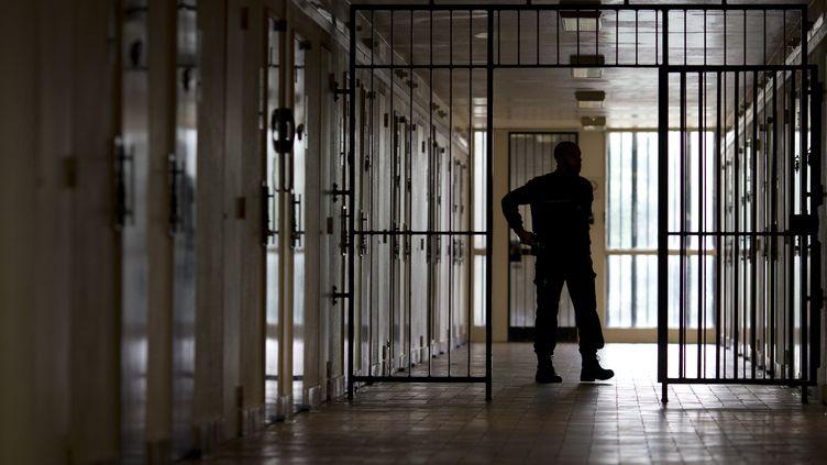 Un surveillant patrouille dans un couloir de la prison de Bois-d'Arcy (Yvelines), le 8 juillet 2014. (KENZO TRIBOUILLARD / AFP)