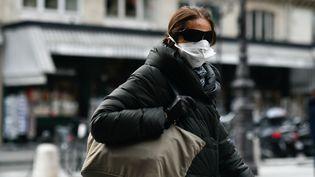 Une femme avec un masque médical marche dans le 13e arrondissement de paris, le 11 mars 2020. (JULIEN MATTIA / AFP)