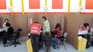 Des patients se font vacciner contre la grippe A (H1N1) dans un gymnase à Paris, le 24 novembre 2009 (LIONEL BONAVENTURE / AFP)