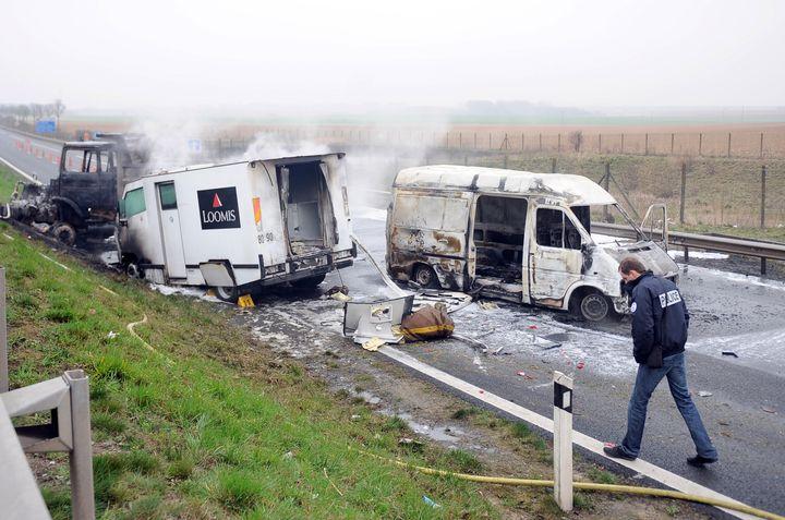 Un policier inspecte les lieux d'un braquage de fourgon blindé, le 17 mars 2011, à Roclincourt (Pas-de-Calais). (DENIS CHARLET / AFP)