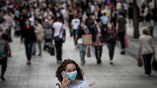 Une jeune femme porte un masque, à Lyon, le 31 août 2020. (JEFF PACHOUD / AFP)