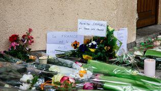 Des gerbes de fleurs déposées devant le collègeoù enseignaitSamuel Paty, le 17 octobre 2020 à Conflans-Sainte-Honorine (Yvelines). (MARIE MAGNIN / HANS LUCAS / AFP)