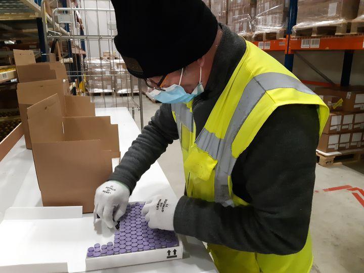 Jean-Claude, préparateur de commande, dispose les flacons de vaccin contre le Covid-19 dans les colis livrés notamment aux Ehpad de Normandie, de Bretagne et des Hauts-de-France. (SOLENNE LE HEN / RADIO FRANCE)