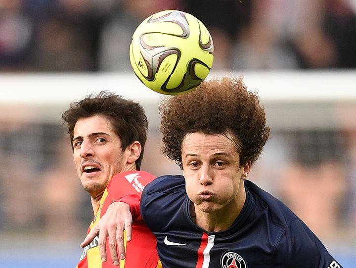 Le Parisien David Luiz à la lutte avec le Lensois Pablo Chavarria, le 7 mars 2015 à Paris. (FRANCK FIFE / AFP)
