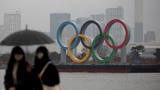 Deux femmes se tiennent non loin du symbole olympique sur l'île d'Odaiba à Tokyo (Japon), le 23 janvier 2021. (KOJI ITO / YOMIURI / AFP)