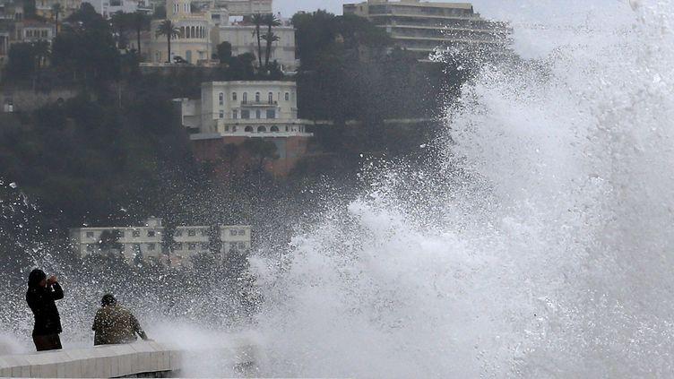 Des personnes près des vagues à Nice (Alpes-Maritimes), le 25 décembre 2013. (VALERY HACHE / AFP)