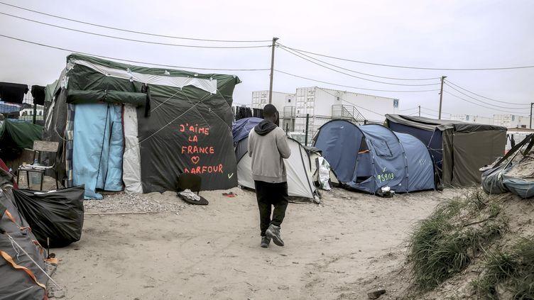 """Un migrant marche à travers la """"jungle"""", le 7 octobre 2016, à Calais (Pas-de-Calais). (PHILIPPE HUGUEN / AFP)"""