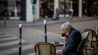 Un homme boit un café sur une terrasse enfin réouverte, le 2 juin 2020 à Paris. (MARTIN BUREAU / AFP)