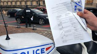 Un policier montre un éthylotest jetable qu'il s'apprête à distribuer à des automobilistes, le 31 décembre 2008, à Montpellier. (PASCAL GUYOT / AFP)