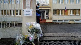 Un gendarme monte la garde près de bouquets de fleurs déposés devant l'entrée de la gendarmerie d'Ambert (Puy-de-Dôme) le 23 décembre 2020. (OLIVIER CHASSIGNOLE / AFP)