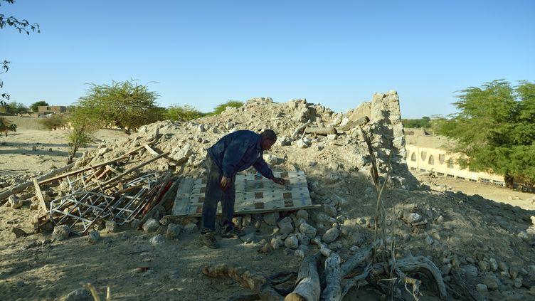 Un homme examine les ruines d'un mausolée détruit par les islamistes, dans un cimetière de Tombouctou, en juillet 2013 (ERIC FEFERBERG / AFP)