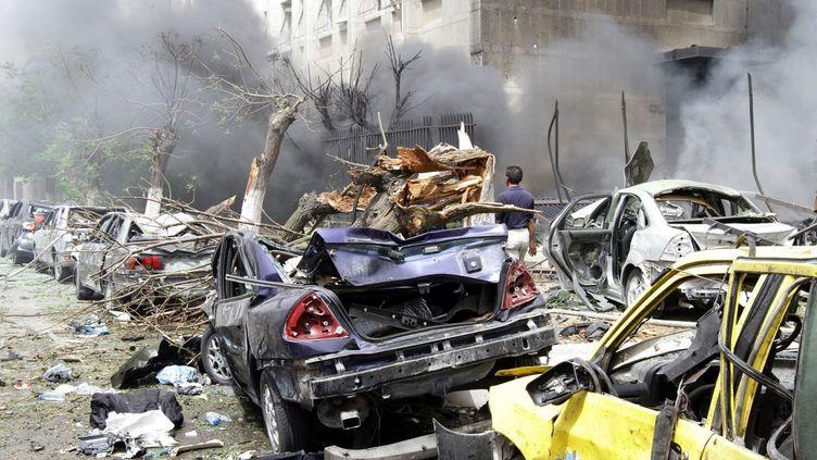 Des voitures détruites lors d'un attentat à la voiture piégée, à Damas, la capitale syrienne, le 8 avril 2013. (LOUAI BESHARA / AFP)