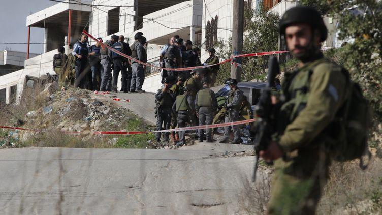 Des soldats israéliens sur le site d'une attaque à la voiture bélier, oeuvre d'un Palestinien, le 27 novembre 2015 à Beit Oummar, en Cisjordanie. (HAZEM BADER / AFP)