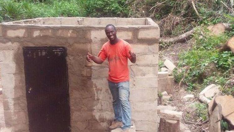 Ibrahima Tounkara devant le micro-barrage hydroélectrique qu'il a construit de ses mains dans son petit village de la région de Guéckédou (sud de la Guinée). (Guinéeinfos)