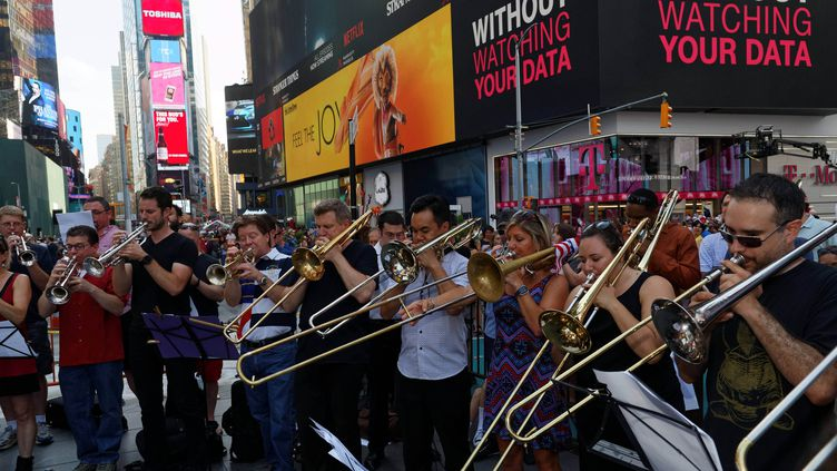 """Un ensemble d'environ cinquante cuivres, constitué par le trompettiste français Dominic Derasse, a interprété le 21 juillet """"La Marseillaise """" à Times Square,  (TREVOR COLLENS / AFP)"""