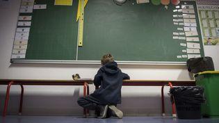 Un jeune élève travaille au pied du tableau dans sa classe. (MARTIN BUREAU / AFP)