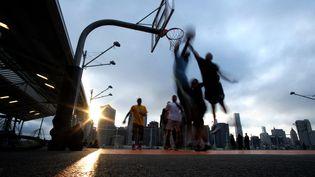 Des jeunes jouent au basket dans un parc deNew-York, le 2 juin 2016. (Jewel SAMAD / AFP)
