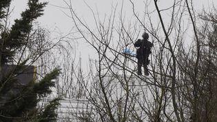 Un officier de police sur le toit d'un immeuble, surveillant le bâtiment dans lequel se sont réfugiés les frères Kouachi à Dammartin-en-Goële, le 9 janvier 2015. (DOMINIQUE FAGET / AFP)