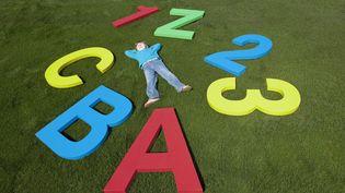 Un enfant couché dans l'herbe, entre chiffres et lettres. (LES AND DAVE JACOBS / CULTURA CREATIVE / AFP)