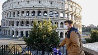 Un cycliste avec un masque contre le coronavirus Covid-19 devant le Colisée de Rome, en Italie, le 11 mars 2020. (RICCARDO DE LUCA / ANADOLU AGENCY / AFP)
