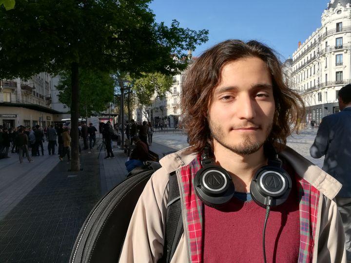 Maël, unétudiant en musicologie et en sciences, s'est arrêté pour écouter Jacques Cheminade, place de la République, à Lyon, le 11 avril 2017. (HUGO CAILLOUX / FRANCEINFO)