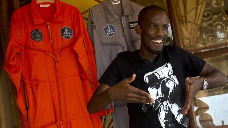 Mandla Maseko parle à un journalistedevant deux combinaisons de la NASA, à Pretoria, la capitale de l'Afrique du Sud, le 9 janvier 2014. (ALEXANDER JOE / AFP)