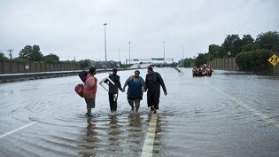 Des habitants de Houston marchent sur une autoroute inondée, le 27 août 2017 à Houston, au Texas (Etats-Unis). (BRENDAN SMIALOWSKI / AFP)