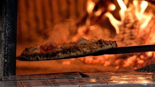 Une pizza sort d'un four à Naples (Italie), le 6 décembre 2017. (TIZIANA FABI / AFP)