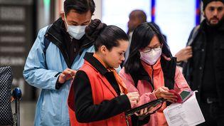 Une employée des Aéroports de Paris aide des passagers qui viennent de Chine, le 26 janvier 2020 à l'aéroport de Roissy-Charles de Gaulle. (ALAIN JOCARD / AFP)