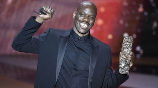"""Jean-Pascal Zadi avec son César du meilleur espoir masculin pour """"Tout simplement noir"""", le 12 mars 2021 à l'Olympia à Paris, lors de la 46e édition de la cérémonie. (BERTRAND GUAY / AFP)"""