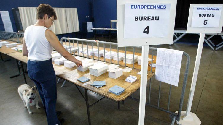 Une électrice choisit des bulletins dans un bureau de vote au Castenet (Haute-Garonne) (ERIC CABANIS / AFP)