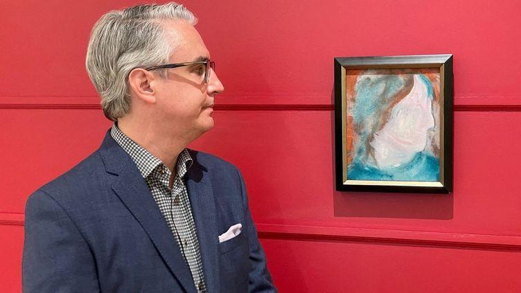Le spécialiste canadien en art Rob Cowley devant une peinture de David Bowie achetée 5 dollars et vendue aux enchères 108 120 dollars (73.600 euros), lors d'une enchère en ligne à Toronto (Canada) en juin 2021. (HANDOUT / COWLEY ABBOTT)