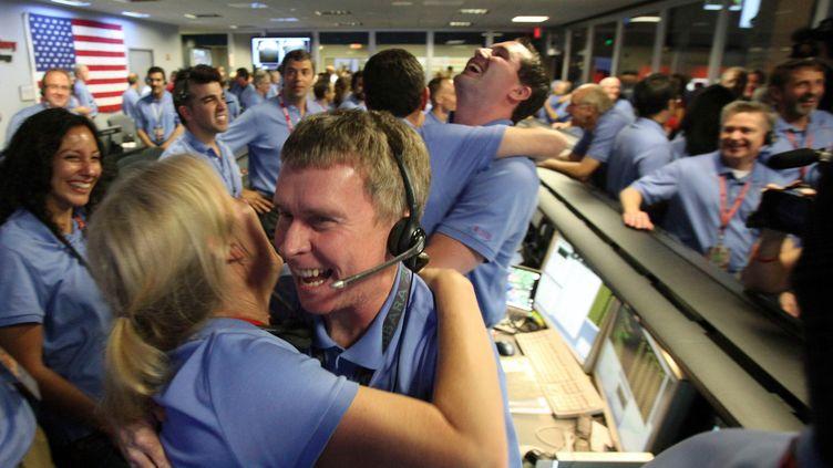 """Explosion de joie dans la salle de contrôle de la Nasa de Pasada, en Californie (Etats-Unis), le 6 août 2012, lors de l'""""amarsissage"""" du robot Curiosity. (BRIAN VAN DER BRUG / AFP)"""