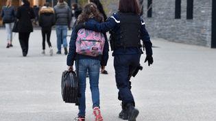 Une élève est accompagnée par une gendarme à son arrivée vendredi au collège Christian Bourquin, à Millas, où une cellule psychologique a été installée. (PASCAL PAVANI / AFP)
