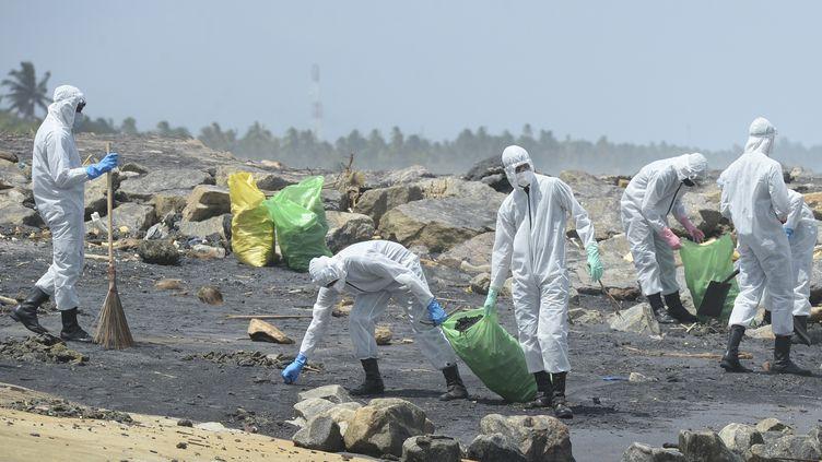 Des militaires sri-lankais nettoient les plages souillées par du plastique, le 30 mai 2021, dans les environs de la capitale Colombo. (LAKRUWAN WANNIARACHCHI / AFP)